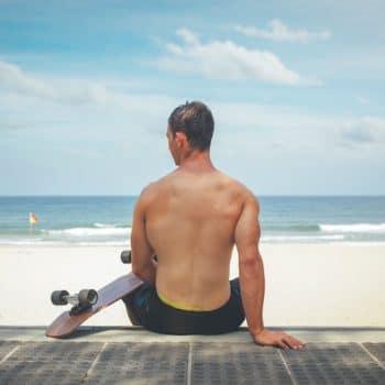 Photograph of a skateboarder sitting on the steps above an Australian beach.