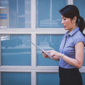 Photograph of an Asian business woman reading something on an ipad, in front of a set of office windows.