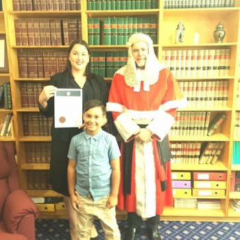 Photograph of Stephanie when she was admitted as a solicitor. She's with a Justice and her son.